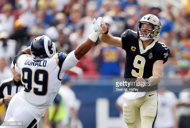 Drew Brees of the New Orleans Saints injures his throwing hand as he is hit by Aaron Donald of the Los Angeles Rams during the first quarter in the...