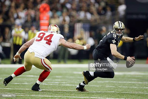 Drew Brees of the New Orleans Saints is pressured by Justin Smith of the San Francisco 49ers during the second quarter of a game at the MercedesBenz...