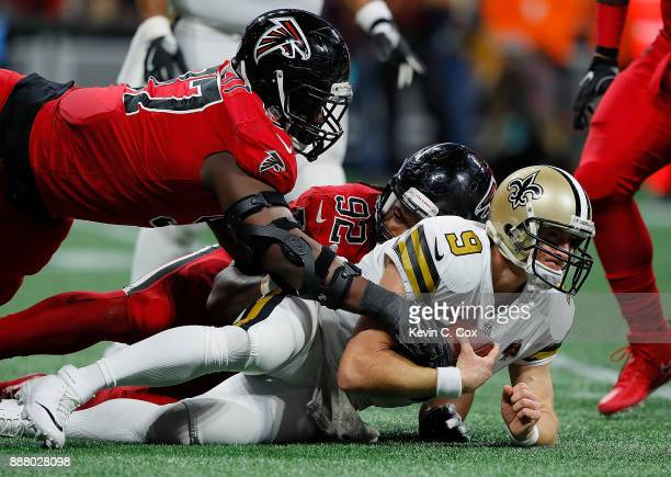 Drew Brees of the New Orleans Saints is sacked by Dontari Poe of the Atlanta Falcons at MercedesBenz Stadium on December 7 2017 in Atlanta Georgia