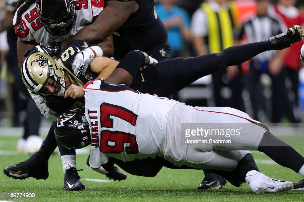 Drew Brees of the New Orleans Saints is sacked by Grady Jarrett of the Atlanta Falcons and Adrian Clayborn during the second half of a game at the...