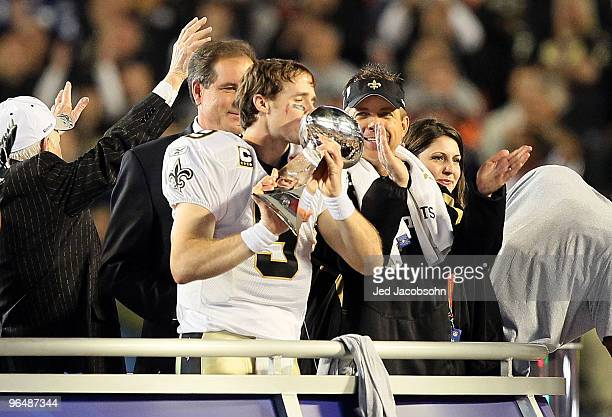 Drew Brees of the New Orleans Saints kisses the Vince Lombardi Trophy as head coach Sean Payton looks on after defeating the Indianapolis Colts...