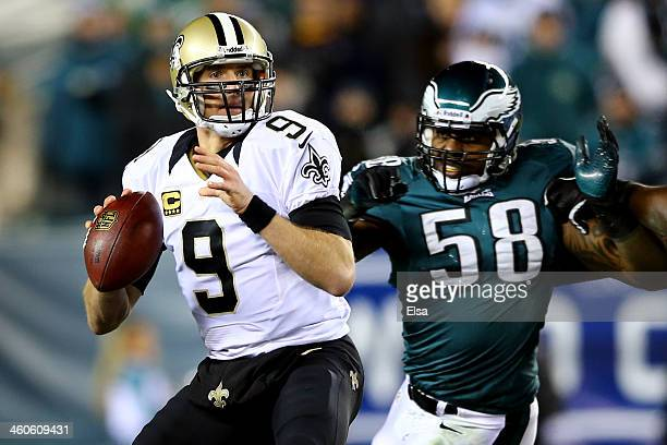 Drew Brees of the New Orleans Saints looks to throw a pass in the first quarter against Trent Cole of the Philadelphia Eagles during their NFC Wild...