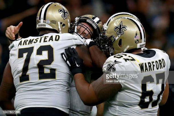 Drew Brees of the New Orleans Saints reacts with Terron Armstead of the New Orleans Saints and Larry Warford of the New Orleans Saints after breaking...