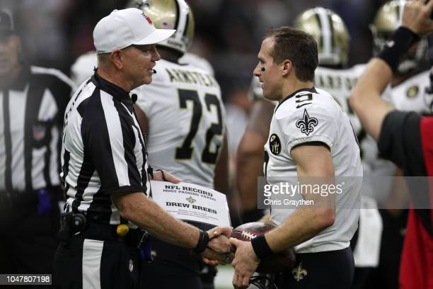 Drew Brees of the New Orleans Saints receives the ball from Referee Charl Cheffers after throwing a 62 yard pass to take the all time passing yards...