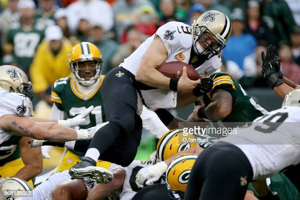Drew Brees of the New Orleans Saints scores a touchdown on a quarterback sneak in the fourth quarter against the Green Bay Packers at Lambeau Field...