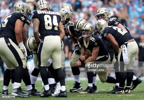 Drew Brees of the New Orleans Saints talks to his teammates in the huddle against the Carolina Panthers during their game at Bank of America Stadium...
