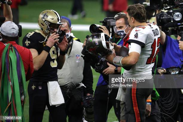 Drew Brees of the New Orleans Saints talks with Tom Brady of the Tampa Bay Buccaneers after their NFC Divisional Playoff game at Mercedes Benz...