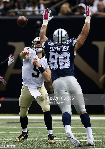 Drew Brees of the New Orleans Saints throws the ball as Tyrone Crawford of the Dallas Cowboys defends during the second quarter against the Dallas...