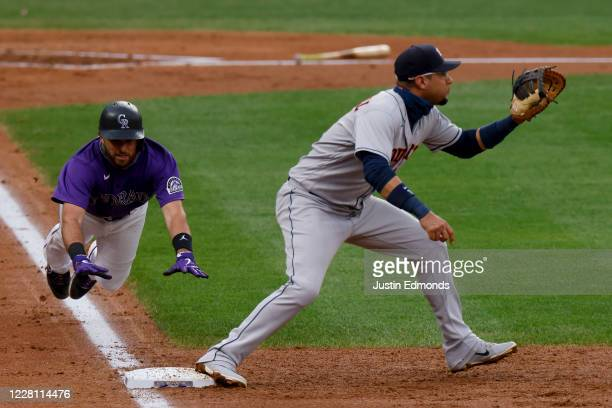 Drew Butera of the Colorado Rockies dives towards the base as first baseman Yuli Gurriel of the Houston Astros stretches for the ball during the...