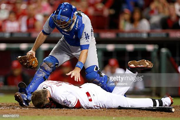 Drew Butera of the Los Angeles Dodgers checks on Zack Cozart of the Cincinnati Reds after he was hit by a pitch in the fifth inning of the game at...