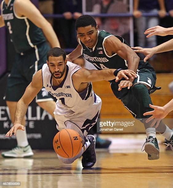 Drew Crawford of the Northwestern Wildcats and Gary Harris of the Michigan State Spartans dive for a loose ball at WelshRyan Arena on January 15 2014...