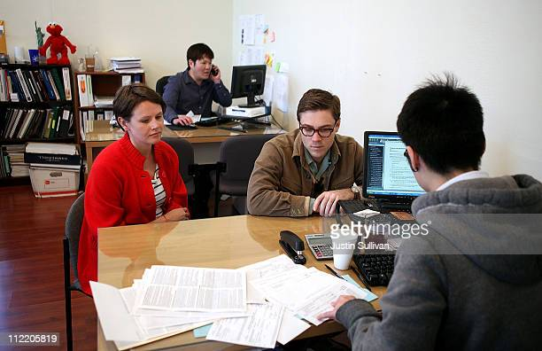 Drew Darmon and his wife Erika Darmon look on as they receive tax preparation assistance from a tax preparer at Liberty Tax on April 14 2011 in San...