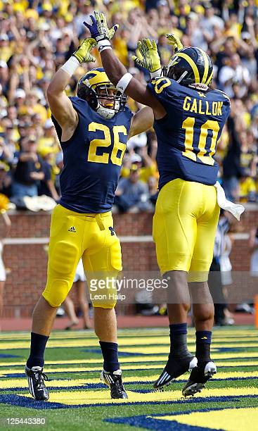 Drew Dileo of the University of Michigan Wolverines celebrates with teammate Jeremy Gallon after scoring on a 19 yard touchdown pass from Denard...