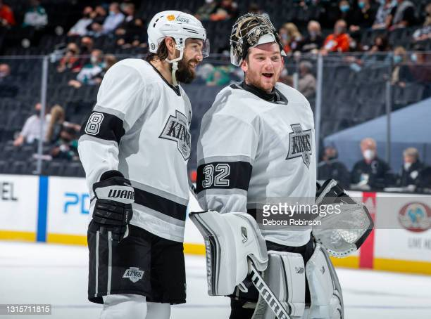 Drew Doughty and goaltender Jonathan Quick of the Los Angeles Kings smile while talking during a break in the the second period of the game against...