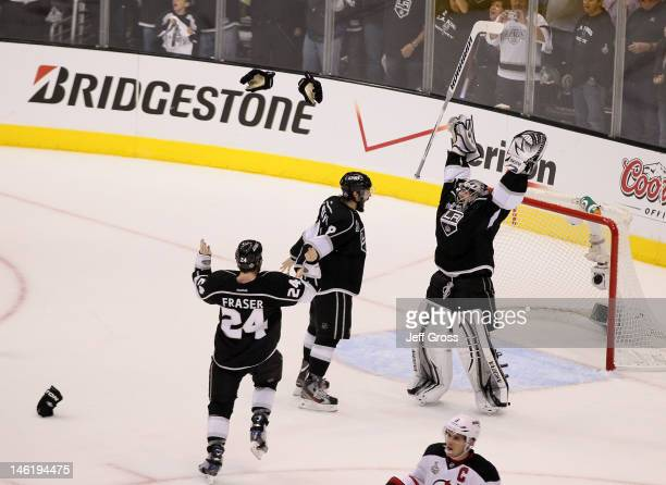Drew Doughty, Jonathan Quick and Colin Fraser of the Los Angeles Kings celebrate the Kings 6-1 victory as Zach Parise of the New Jersey Devils looks...