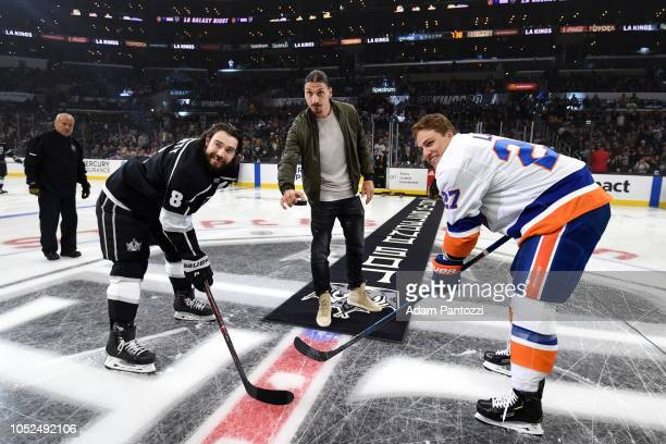 Drew Doughty of the Los Angeles Kings and Anders Lee of the New York Islanders pose for a ceremonial puck drop by Zlatan Ibrahimovic of Los Angeles...