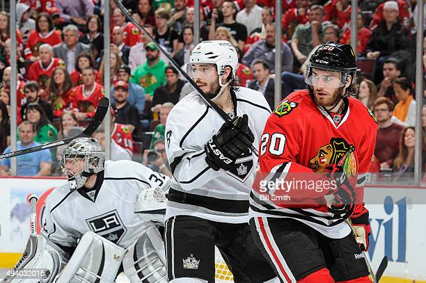 Drew Doughty of the Los Angeles Kings and Brandon Saad of the Chicago Blackhawks watch for the puck next to goalie Jonathan Quick of the Kings in...
