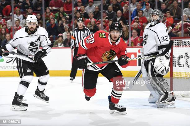 Drew Doughty of the Los Angeles Kings and Brandon Saad of the Chicago Blackhawks watch for the puck next to goalie Jonathan Quick in the first period...