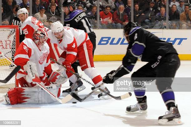 Drew Doughty of the Los Angeles Kings attempts a shot on goal against Jimmy Howard of the Detroit Red Wings during the game at Staples Center on...