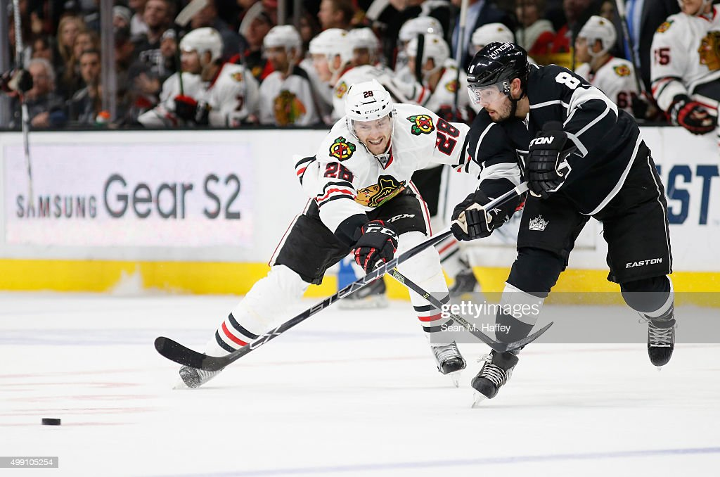 Drew Doughty #8 of the Los Angeles Kings battles Ryan Garbutt #28 of the Chicago Blackhawks for a loose puck during the third period of a game at Staples Center on November 28, 2015 in Los Angeles, California.