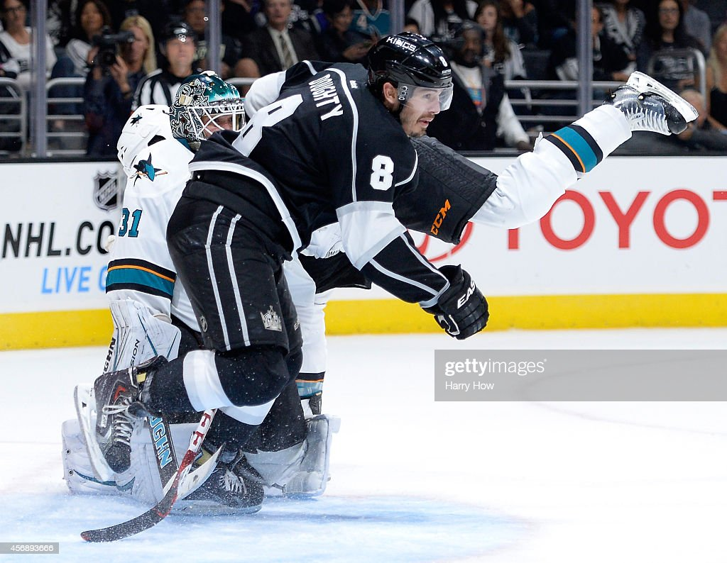 Drew Doughty #8 of the Los Angeles Kings collides with Antti Niemi #31 and Brent Burns #88 of the San Jose Sharks during the second period at Staples Center on October 8, 2014 in Los Angeles, California.