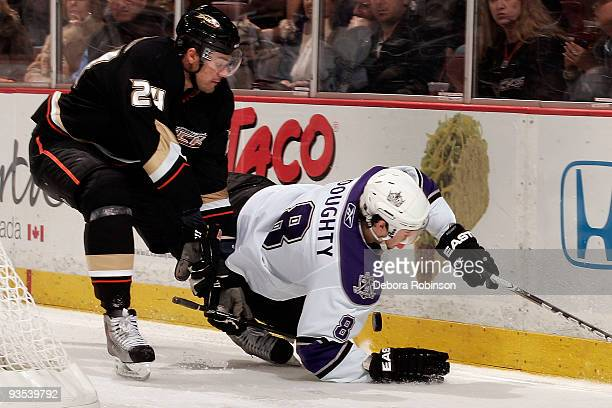 Drew Doughty of the Los Angeles Kings falls to the ice trying to gain control of the puck against Evgeny Artyukhin of the Anaheim Ducks during the...