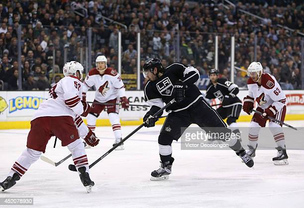 Drew Doughty of the Los Angeles Kings follows through on his shot against Derek Morris of the Phoenix Coyotes during the NHL game at Staples Center...