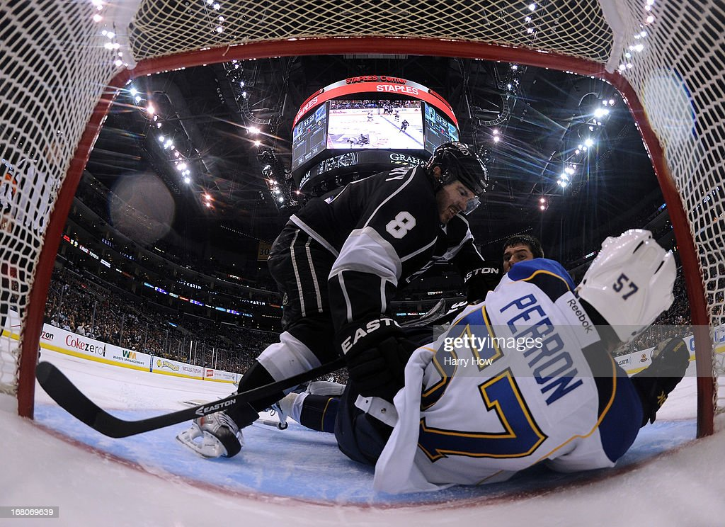 Drew Doughty #8 of the Los Angeles Kings knocks David Perron #57 of the St. Louis Blues into the goal after a collision with Jonathan Quick #32 during the third period in a 1-0 win over the St. Louis Blues in Game Three of the Western Conference Quarterfinals during the 2013 NHL Stanley Cup Playoffs at Staples Center on May 4, 2013 in Los Angeles, California.
