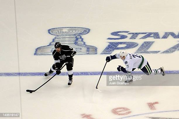 Drew Doughty of the Los Angeles Kings skates with the puck against Mason Raymond of the Vancouver Canucks in Game Four of the Western Conference...