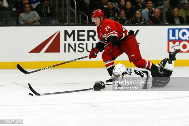 Drew Doughty of the Los Angeles Kings slides to reach the puck as Brock McGinn of the Carolina Hurricanes follows during the second period at Staples...