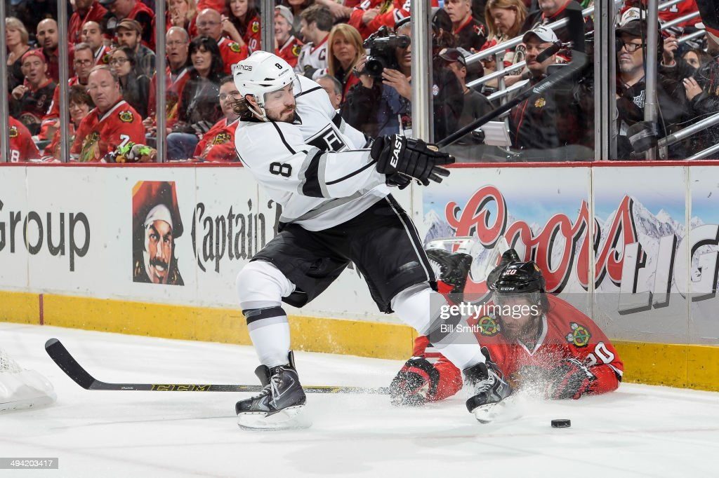 Drew Doughty #8 of the Los Angeles Kings swings at the puck as Brandon Saad #20 of the Chicago Blackhawks lays on the ice in Game Five of the Western Conference Final during the 2014 NHL Stanley Cup Playoffs at the United Center on May 28, 2014 in Chicago, Illinois.