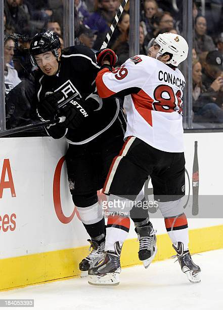 Drew Doughty of the Los Angeles Kings takes a hit from Cory Conacher of the Ottawa Senators at Staples Center on October 9 2013 in Los Angeles...