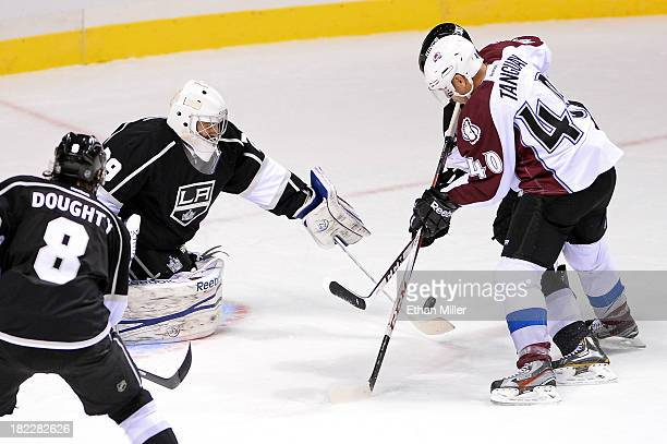 Drew Doughty of the Los Angeles Kings watches as goalie Mathieu Garon deflects a shot by Alex Tanguay of the Colorado Avalanche during their...