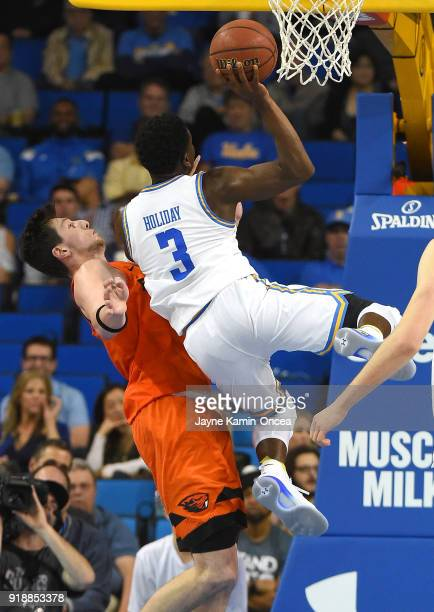 Drew Eubanks of the Oregon State Beavers defends Aaron Holiday of the UCLA Bruins as he goes for a basket in the second half of the game at Pauley...