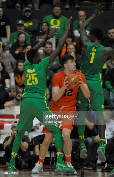 Drew Eubanks of the Oregon State Beavers tries to get around Chris Boucher and Jordan Bell of the Oregon Ducks during the second half of the game at...
