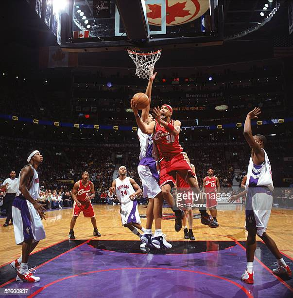 Drew Gooden of the Cleveland Cavaliers goes to the basket past Loren Woods of the Toronto Raptors during a game at Air Canada Centre on March 20 2005...
