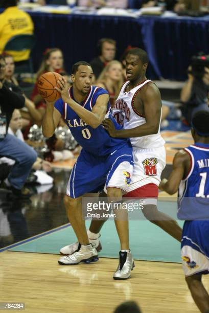 Drew Gooden of the Kansas Jayhawks holds the ball away from Tahj Holden of the Maryland Terrapins during the semifinal round of the NCAA Men's Final...