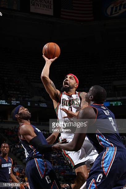 Drew Gooden of the Milwaukee Bucks shoots against Hakim Warrick and DeSagana Diop of the Charlotte Bobcats during the game on December 7 2012 at the...