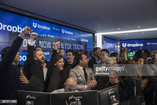 Drew Houston chief executive officer and cofounder of Dropbox Inc second left and Arash Ferdowsi cofounder of Dropbox Inc third left react with...