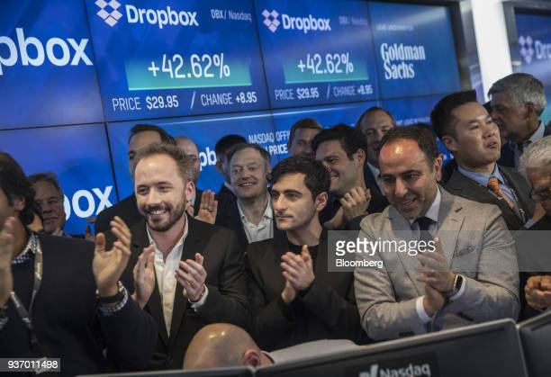 Drew Houston chief executive officer and cofounder of Dropbox Inc center left and Arash Ferdowsi cofounder of Dropbox Inc center applaud with...