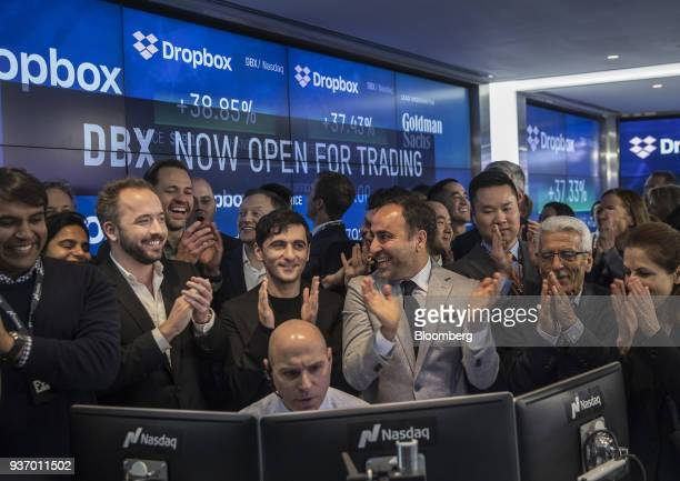 Drew Houston chief executive officer and cofounder of Dropbox Inc second left and Arash Ferdowsi cofounder of Dropbox Inc third left applaud with...