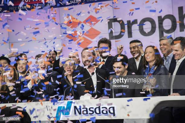 Drew Houston chief executive officer and cofounder of Dropbox Inc center and Arash Ferdowsi cofounder of Dropbox Inc center right react during the...