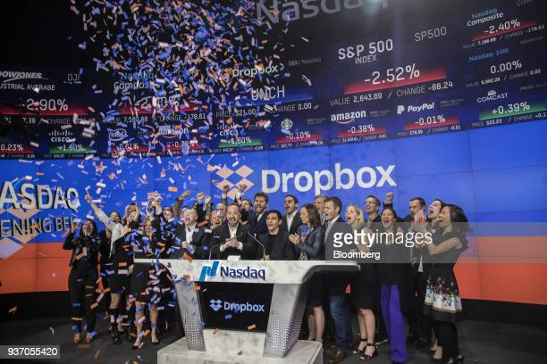 Drew Houston chief executive officer and cofounder of Dropbox Inc center left and Arash Ferdowsi cofounder of Dropbox Inc center right applaud with...
