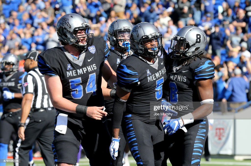 Drew Kyser #54, Sean Dykes #5 and Darrell Henderson #8 of the Memphis Tigers celebrate a touchdown against the East Carolina Pirates on November 25, 2017 at Liberty Bowl Memorial Stadium in Memphis, Tennessee.