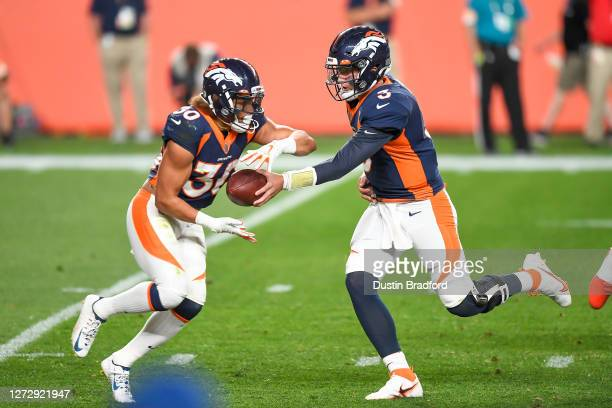 Drew Lock of the Denver Broncos hands off to Phillip Lindsay against the Tennessee Titans at Empower Field at Mile High on September 14, 2020 in...
