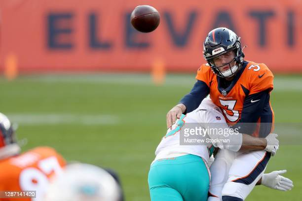Drew Lock of the Denver Broncos is hit by Kyle Van Noy of the Miami Dolphins as he throws during the second quarter at Empower Field At Mile High on...