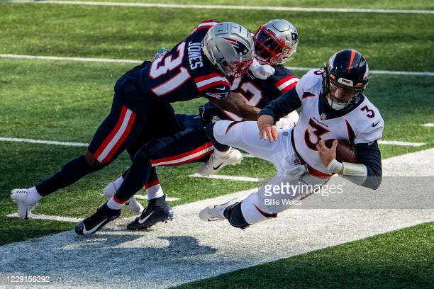 Drew Lock of the Denver Broncos is tackled by Jonathan Jones and Devin McCourty of the New England Patriots during the second half of a game at...