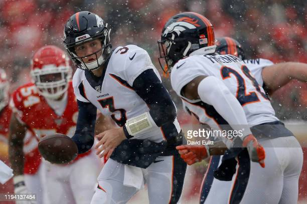 Drew Lock of the Denver Broncos looks to hand the ball off to Royce Freeman in the game against the Kansas City Chiefs at Arrowhead Stadium on...