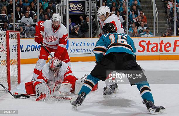 Drew Miller, Brad Stuart and Jimmy Howard of the Detroit Red Wings defend the net against Devin Setoguchi of the San Jose Sharks in Game Five of the...
