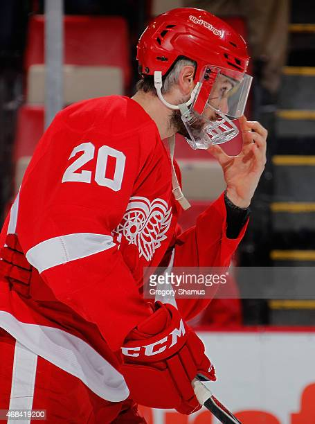 Drew Miller of the Detroit Red Wings adjusts his protective face mask after taking around 60 stitches from a skate cut on his face last game last...